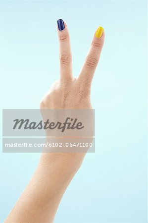 Womans hand making victory sign Stock Photo - Premium Royalty-Free, Image code: 6102-06471100