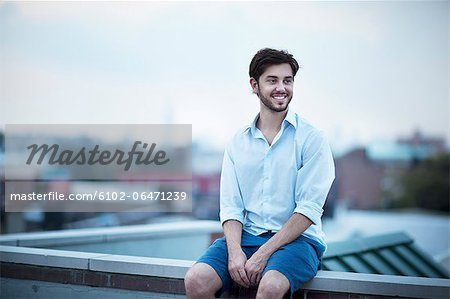 Young smiling man looking away Stock Photo - Premium Royalty-Free, Image code: 6102-06471239