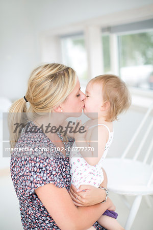Mother kissing her daughter Stock Photo - Premium Royalty-Free, Image code: 6102-06777270