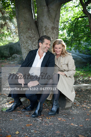 Smiling mature couple sitting Stock Photo - Premium Royalty-Free, Image code: 6102-06777313