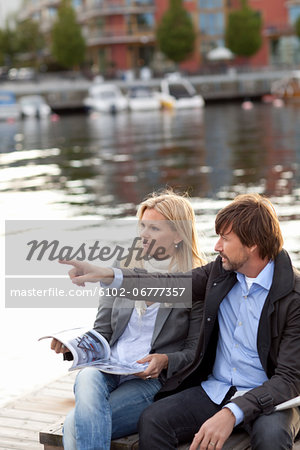 Couple sitting by water Stock Photo - Premium Royalty-Free, Image code: 6102-06777357