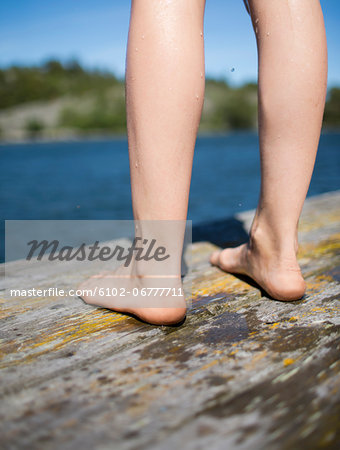 Girls feet on jetty, close-up Stock Photo - Premium Royalty-Free, Image code: 6102-06777711