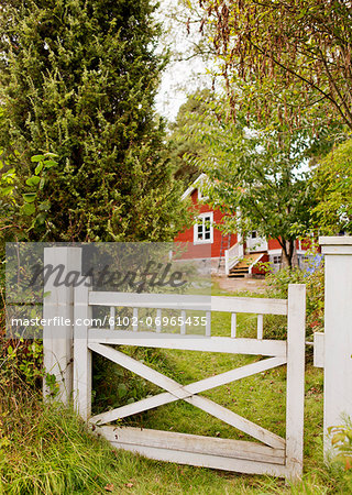 Wooden gate with red cottage in background Stock Photo - Premium Royalty-Free, Image code: 6102-06965435