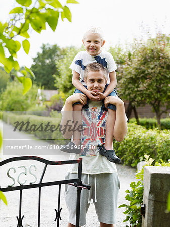 Teenage boy carrying younger brother on shoulders Stock Photo - Premium Royalty-Free, Image code: 6102-06965480