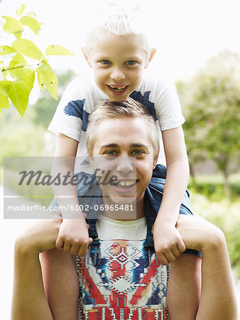 Teenage boy carrying younger brother on shoulders Stock Photo - Premium Royalty-Free, Image code: 6102-06965481