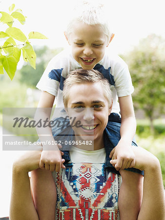 Teenage boy carrying younger brother on shoulders Stock Photo - Premium Royalty-Free, Image code: 6102-06965482