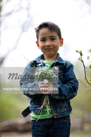 Smiling boy holding flowers Stock Photo - Premium Royalty-Free, Image code: 6102-06965586