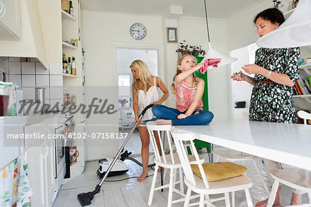 Mother with daughters tidy up Stock Photo - Premium Royalty-Free, Image code: 6102-07158137