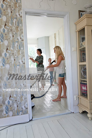 Mother with daughters tidy up Stock Photo - Premium Royalty-Free, Image code: 6102-07158139