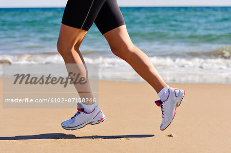 Young woman running on beach, low section, Algarve, Portugal Stock Photo - Premium Royalty-Free, Image code: 6102-07158246