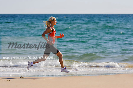 Young woman running on beach, Algarve, Portugal Stock Photo - Premium Royalty-Free, Image code: 6102-07158251