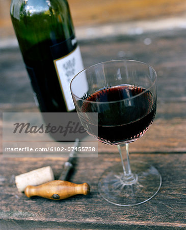 High angle view of red wine in glass and corkscrew Stock Photo - Premium Royalty-Free, Image code: 6102-07455738