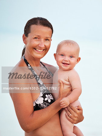 Mother with baby looking at camera, Thailand Stock Photo - Premium Royalty-Free, Image code: 6102-07602782
