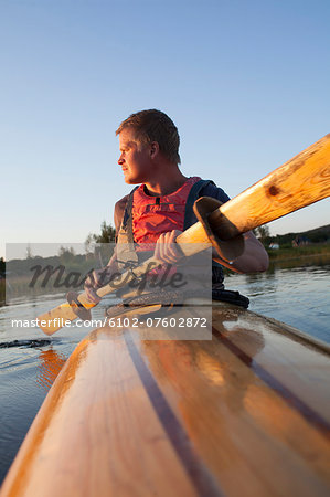 Young man kayaking, Sweden Stock Photo - Premium Royalty-Free, Image code: 6102-07602872