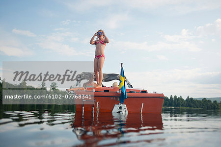 Girl stsnding on a small boat Stock Photo - Premium Royalty-Free, Image code: 6102-07768341