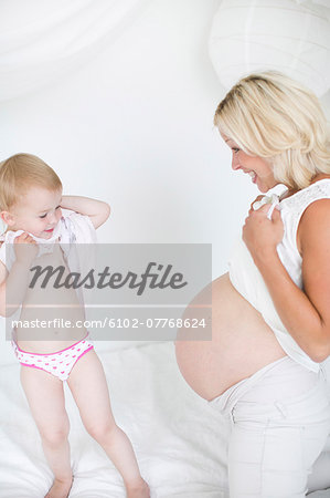 Pregnant mother with daughter, studio shot Stock Photo - Premium Royalty-Free, Image code: 6102-07768624