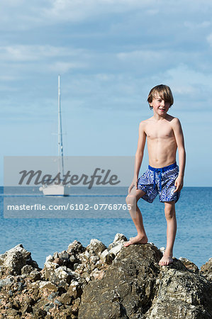 Boy on top of rock, Sicily, Italy Stock Photo - Premium Royalty-Free, Image code: 6102-07768765