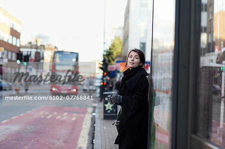 Young woman standing on bus stop Stock Photo - Premium Royalty-Free, Image code: 6102-07768841