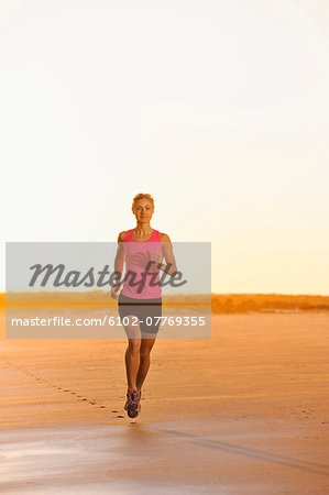 Woman running on beach at dusk Stock Photo - Premium Royalty-Free, Image code: 6102-07769355