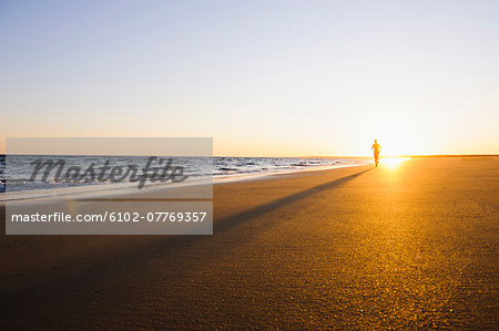 Woman running on beach at sunset Stock Photo - Premium Royalty-Free, Image code: 6102-07769357