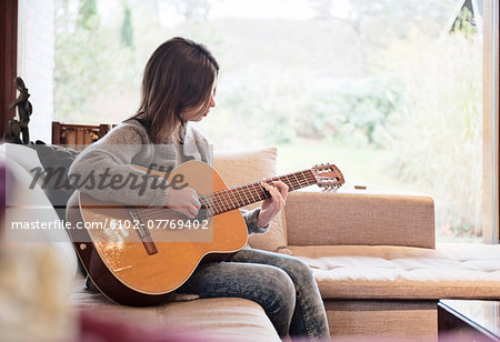 Teenage girl playing guitar Stock Photo - Premium Royalty-Free, Image code: 6102-07769402