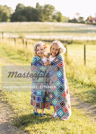 Two girls wrapped together in blanket Stock Photo - Premium Royalty-Free, Image code: 6102-07769468
