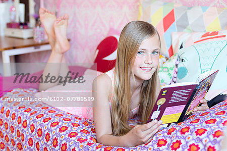 Girl reading in her room Stock Photo - Premium Royalty-Free, Image code: 6102-07789599