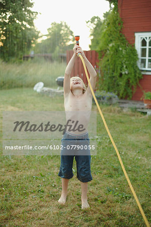 Boy playing with garden hose in garden Stock Photo - Premium Royalty-Free, Image code: 6102-07790055