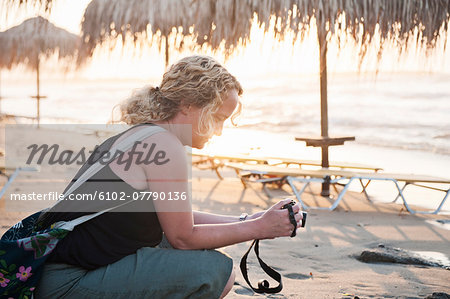 Woman on beach looking at camera Stock Photo - Premium Royalty-Free, Image code: 6102-07790136