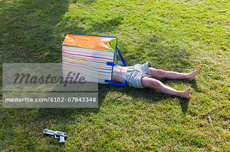 Boy with carrier bag on head Stock Photo - Premium Royalty-Free, Image code: 6102-07843348