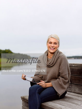 Smiling woman on jetty with digital tablet Stock Photo - Premium Royalty-Free, Image code: 6102-07843570