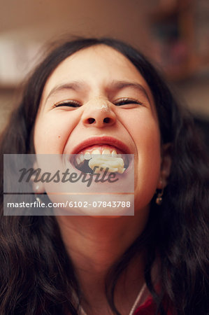 Portrait of smiling girl with cookie in her mouth Stock Photo - Premium Royalty-Free, Image code: 6102-07843788