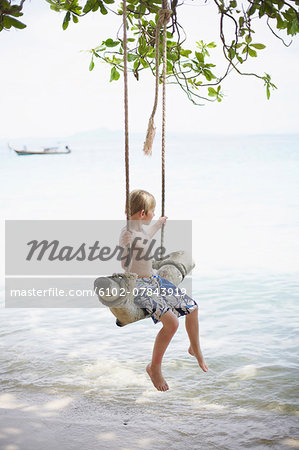 Boy on swing at beach Stock Photo - Premium Royalty-Free, Image code: 6102-07843919