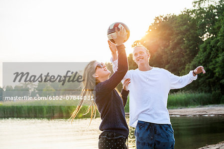 Young couple playing ball at water Stock Photo - Premium Royalty-Free, Image code: 6102-07844031