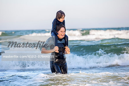 Mother carrying son on shoulders in sea Stock Photo - Premium Royalty-Free, Image code: 6102-07844035