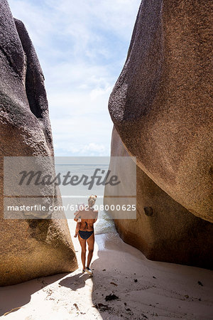 Mother with child walking on beach Stock Photo - Premium Royalty-Free, Image code: 6102-08000625