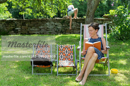 Woman reading book on sun chair Stock Photo - Premium Royalty-Free, Image code: 6102-08000909