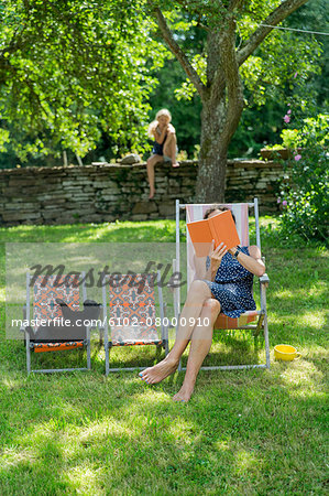 Woman reading book on sun chair Stock Photo - Premium Royalty-Free, Image code: 6102-08000910