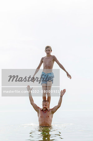 Teenager standing on fathers shoulders in water Stock Photo - Premium Royalty-Free, Image code: 6102-08000931