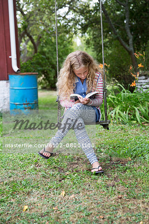 Girl on swing reading book Stock Photo - Premium Royalty-Free, Image code: 6102-08001100