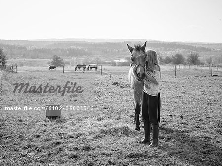 Girl with horse on pasture Stock Photo - Premium Royalty-Free, Image code: 6102-08001346