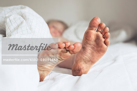 Childs dirty feet in bed Stock Photo - Premium Royalty-Free, Image code: 6102-08001449