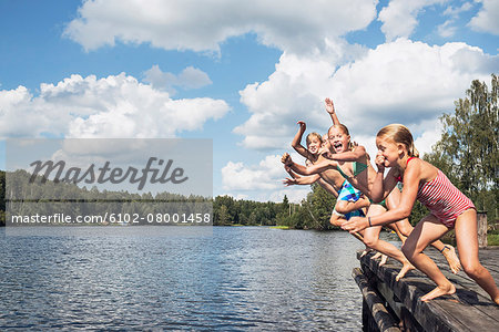 Boys and girls jumping into water Stock Photo - Premium Royalty-Free, Image code: 6102-08001458
