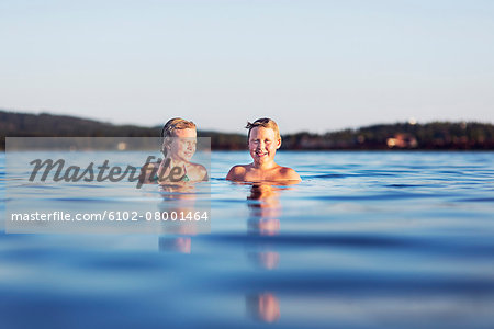 Girl and boy in lake Stock Photo - Premium Royalty-Free, Image code: 6102-08001464