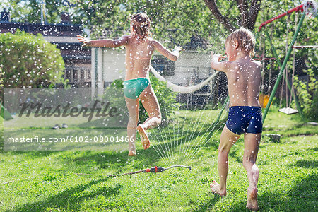 Boy and girl playing in garden Stock Photo - Premium Royalty-Free, Image code: 6102-08001466