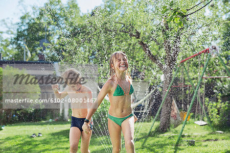 Girl and boy playing with water in garden Stock Photo - Premium Royalty-Free, Image code: 6102-08001467