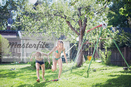 Girl and boy playing with water in garden Stock Photo - Premium Royalty-Free, Image code: 6102-08001468