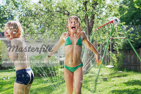 Girl and boy playing with water in garden Stock Photo - Premium Royalty-Free, Image code: 6102-08001469
