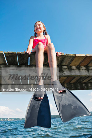 girl wearing flippers on jetty Stock Photo - Premium Royalty-Free, Image code: 6102-08063041