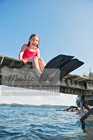Happy girl wearing flippers on jetty Stock Photo - Premium Royalty-Free, Image code: 6102-08063042